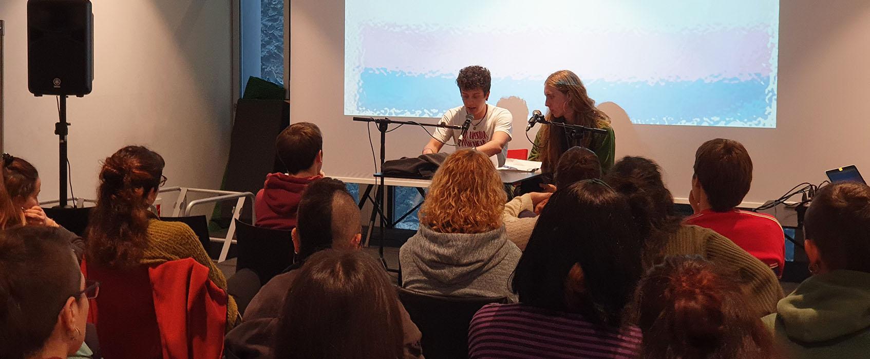 Fotografia on surten dues persones amb un micròfon al davant fent la ponència introductòria a les jornades. Veiem també unes quantes persones del públic.